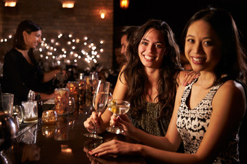 Portrait Of Female Friends On Night Out At Cocktail Bar