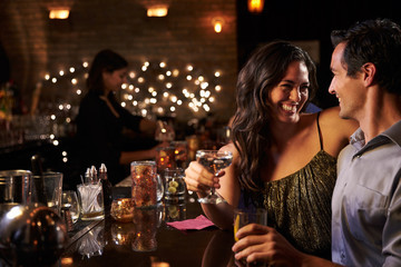 Couple Enjoying Night Out At Cocktail Bar