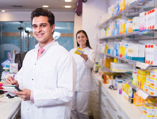 Two pharmacists in modern pharmacy.