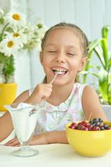 Girl eating sweet  dessert with berries