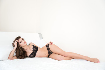 Woman in sexy black lingerie lying on the bed