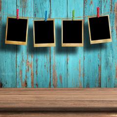 Old picture frame hanging on clothesline on wood background.