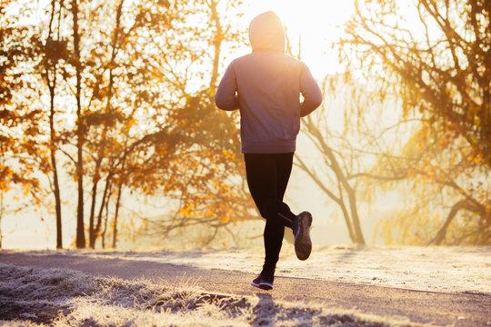 Young man running during autumn, winter morning