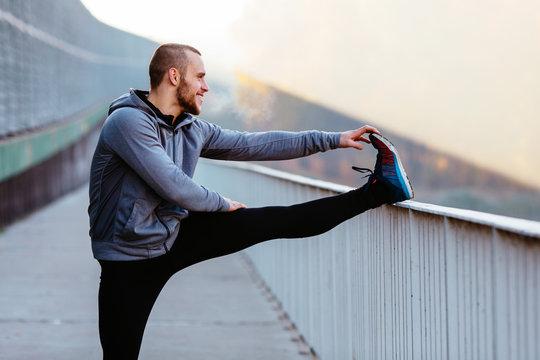 Athletic runner doing stretching exercise, preparing for morning