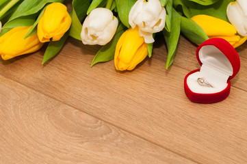 Tulips and silver engagement ring on a wooden background