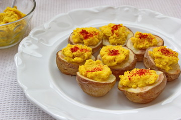hummus with pepper served on baked potatoes