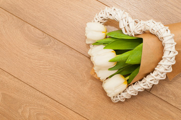 Fresh tulips flowers and decorative heart on wooden planks. Selective focus. St. Valentines or love concept.
