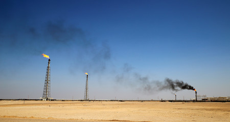 A flare stack burning off excess gas at an oil refinery in the desert of the Middle East