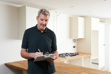 Carpenter Installing Luxury Fitted Kitchen