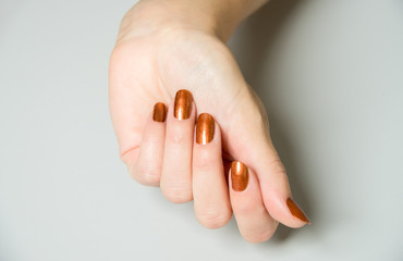 Hands with brown metallic paint on fingernails