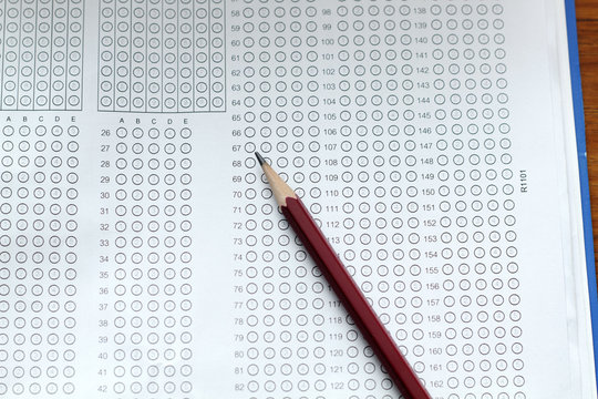 glasses and pencil on Standardized test form with answers bubble