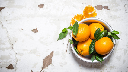 Fresh oranges with leaves in a bowl.