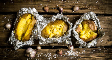 Baked potatoes in foil on a wooden table .