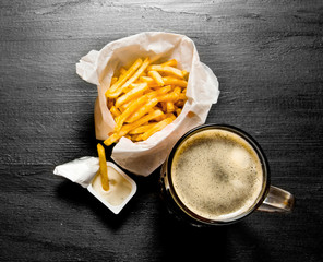 Fresh beer and fries with mustard sauce on chalkboard.