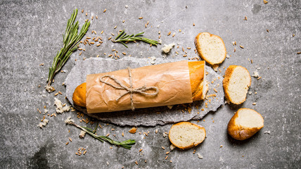 Fresh ciabatta with rosemary on a stone stand.
