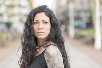 Portrait of sensual tattooed woman looking away.