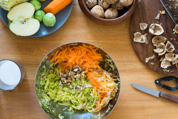 Carrot, savoy cabbage, brussels sprouts, apple and walnuts in a metal bowl