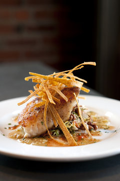 Seared Halibut fillet with spices and sauce on a bed of mixed beans and crispy tortilla strips