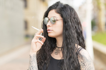 Smoking tattooed sensual beautiful woman, outdoor.