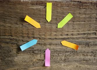Unbeschriebene Post-Its in verschiedenen Farben auf Holz Hintergrund