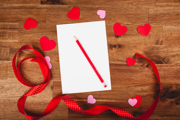 Valentines day white paper with red hearts and pen on wooden table