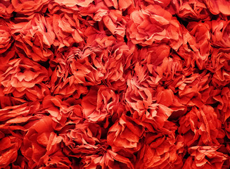 background of flowers made from red a crepe paper. pleated paper decorations closeup, texture