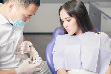 Dentist doctor shows the patient's jaw with teeth