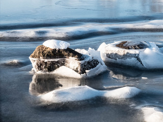Frozen sea at the shore with rocks