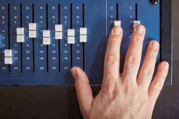 Fingers of audio engineer pushing the faders of an auio mixer