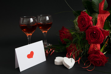 Red roses, glasses of wine and valentine's card on black background. Valentine's day decoration.