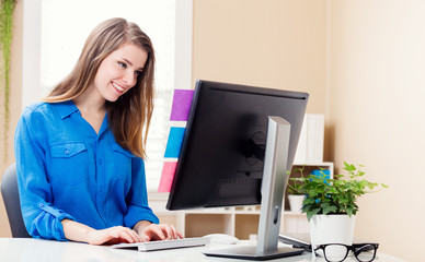 Happy young woman working in her home office