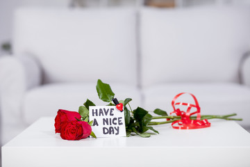 Red roses on the table with note Have a nice day