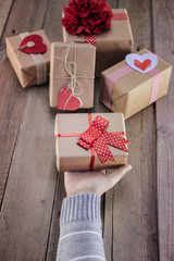 Female hands holding gift on wooden table