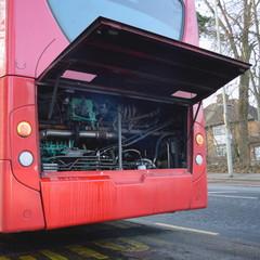 Damaged red public bus with open bonnet