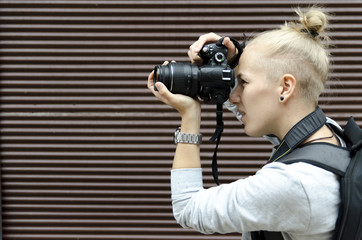 Young woman taking pictures with professional camera