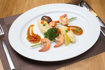 A steak shrimp with  fresh with fresh vegetables on a white plat