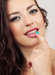Beautiful girl is biting her finger attractively. She is looking at the camera with temptation.