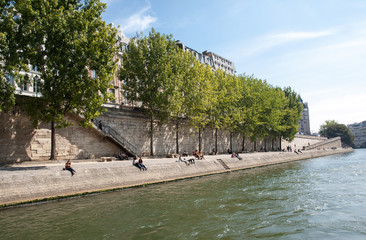 People are enjoying their free time on the banks of river Seine, in Paris, France.