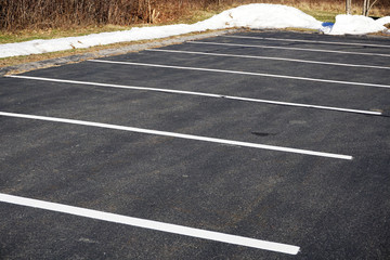 empty parking lot in winter with snow piles outside