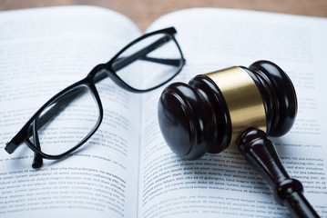 Mallet And Eyeglasses On Open Legal Book
