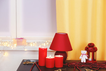 Colourful Christmas decorations and candles on the table against window decorated with glowing lights, close up