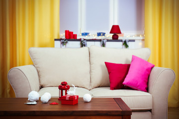 Colourful decorated interior. Comfortable living room, table with Christmas decorations on it is close up