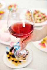 Woman holding wineglass on buffet background