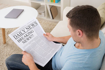 Man Reading Breaking News On Newspaper At Home