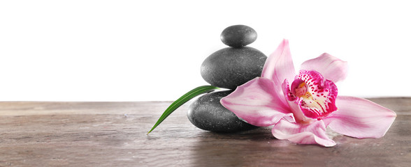 Spa pebbles and beautiful pink orchid on white background