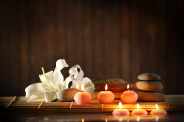 Spa still life with stones, candles and flowers in water on wooden blurred background