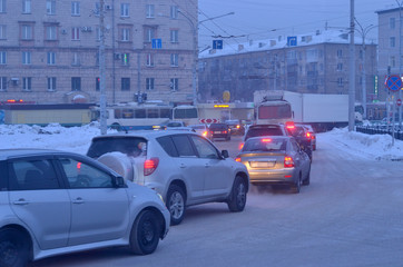 Cars in the city, twilight. Cars on the forecourt of the city. The end of the working day, dusk. Winter. The air emissions from the smoke, frost, urban smog. Russia Siberia.