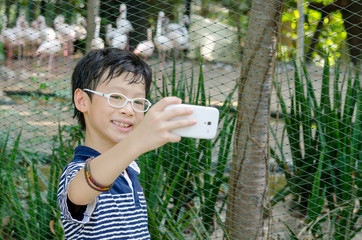 Young Asian boy take photo himself by smartphone