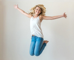 Beautiful young girl smiling while leaping in air barefoot