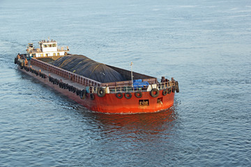 Iron ore mined in hinterland transported to the main harbor in large cargo boat for loading into big ships for exporting in India